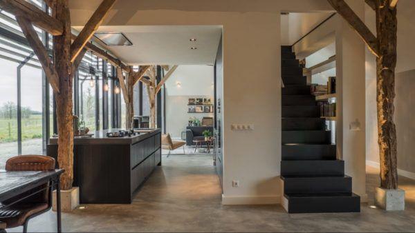 Ancienne ferme rénovée style industriel mur de briques poutres apparentes et sol de béton ciré escaliers noirs