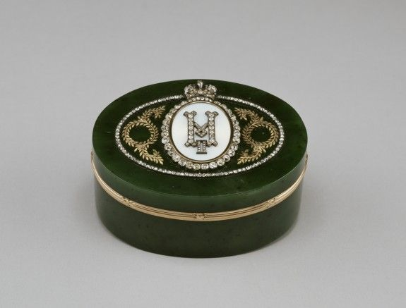 The monogram of Nicholas II, rendered in diamonds, is set in the lid of this presentation box. It is mounted in an opalescent white cartouche bordered by diamonds and surmounted by the Imperial crown, also in diamonds. The central cartouche is flanked by green gold wreaths and garlands and is enclosed within an oval border of rose-cut diamonds.
