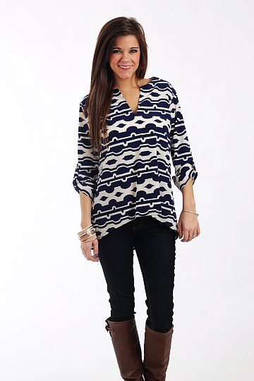 """Pleasant Patterns Blouse, Navy $42.00  This blouse is a timeless addition to your closet! The navy and white patterned top is trendy-but-classic and we love the tabbed sleeves, v neck and asymmetrical hemline. Dress it up or down, this piece is a safe bet no matter the occasion!   Fits true to size. Miranda is wearing a small.   From shoulder to hem:  Small - 24""""  Medium - 25""""  Large - 26"""""""