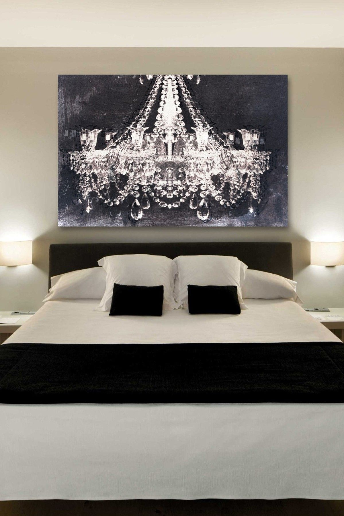 The chandelier art gives such a romantic touch to this bedroom