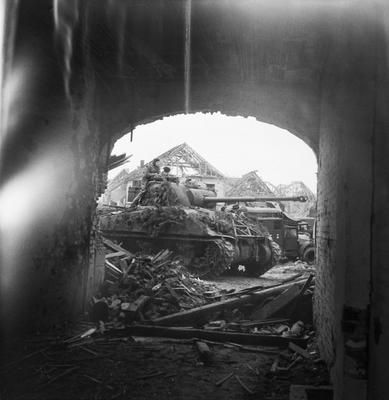 Sherman Firefly tank seen through an archway in the ruined town of Uedem, during the advance to the Rhine, 1 March 1945. Probably a Firefly from the 11th Armoured Division