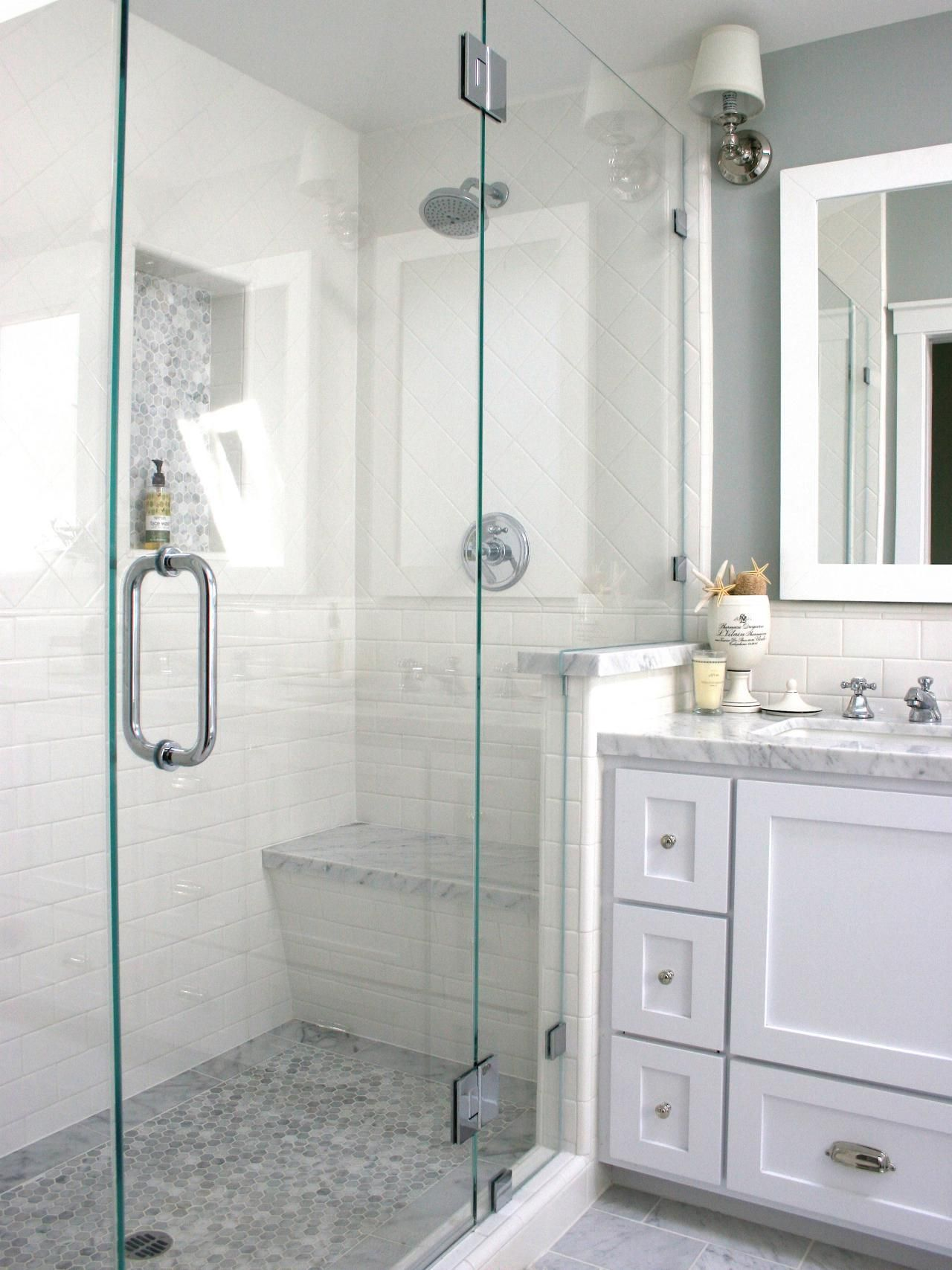 A Glass Enclosed Shower With White Tile Walls And A Gray Mosaic