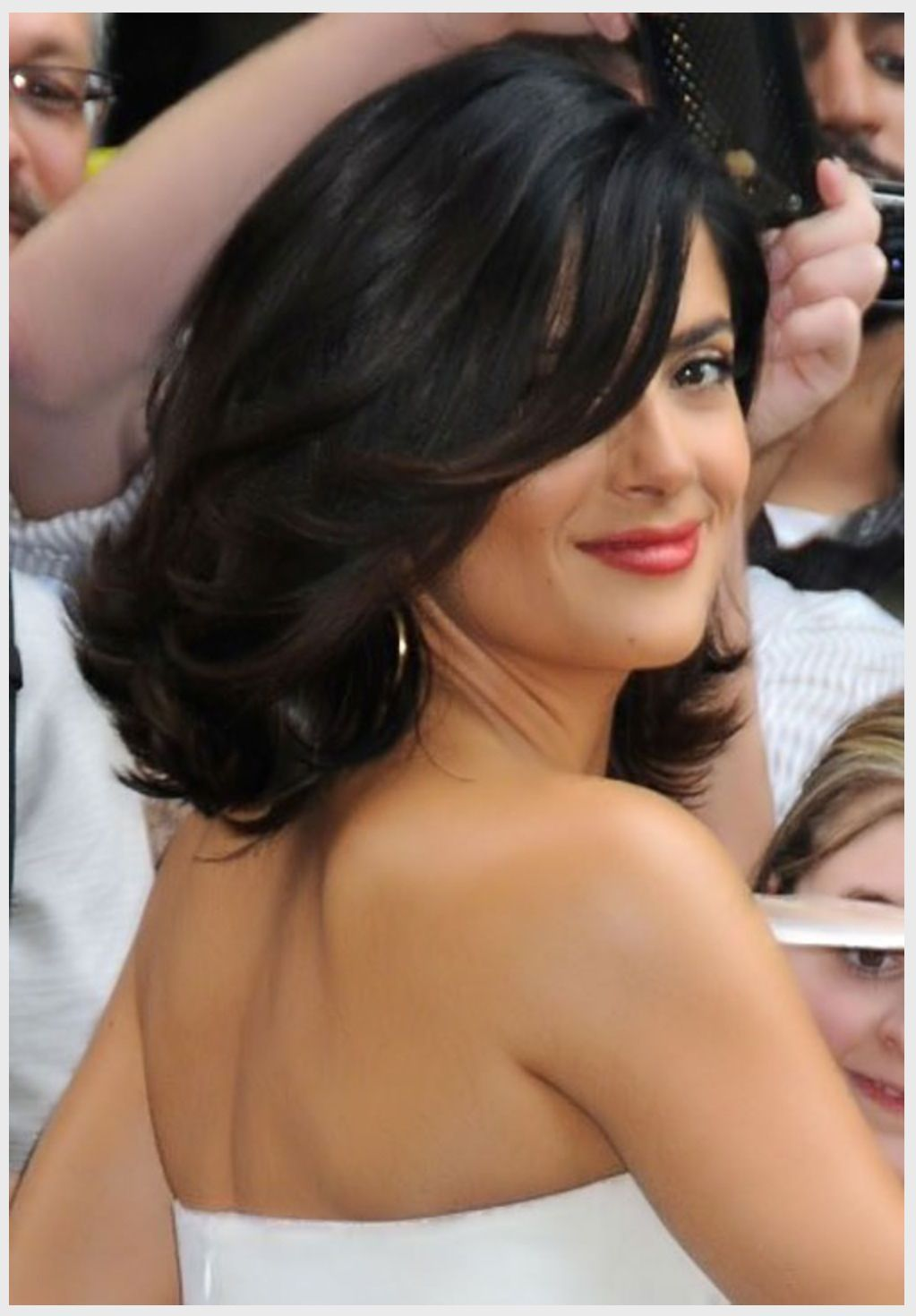 feathers and outward curls on shoulder length hair