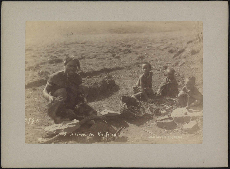 Groepsportret van smid met drie kinderen, zittend op de grond