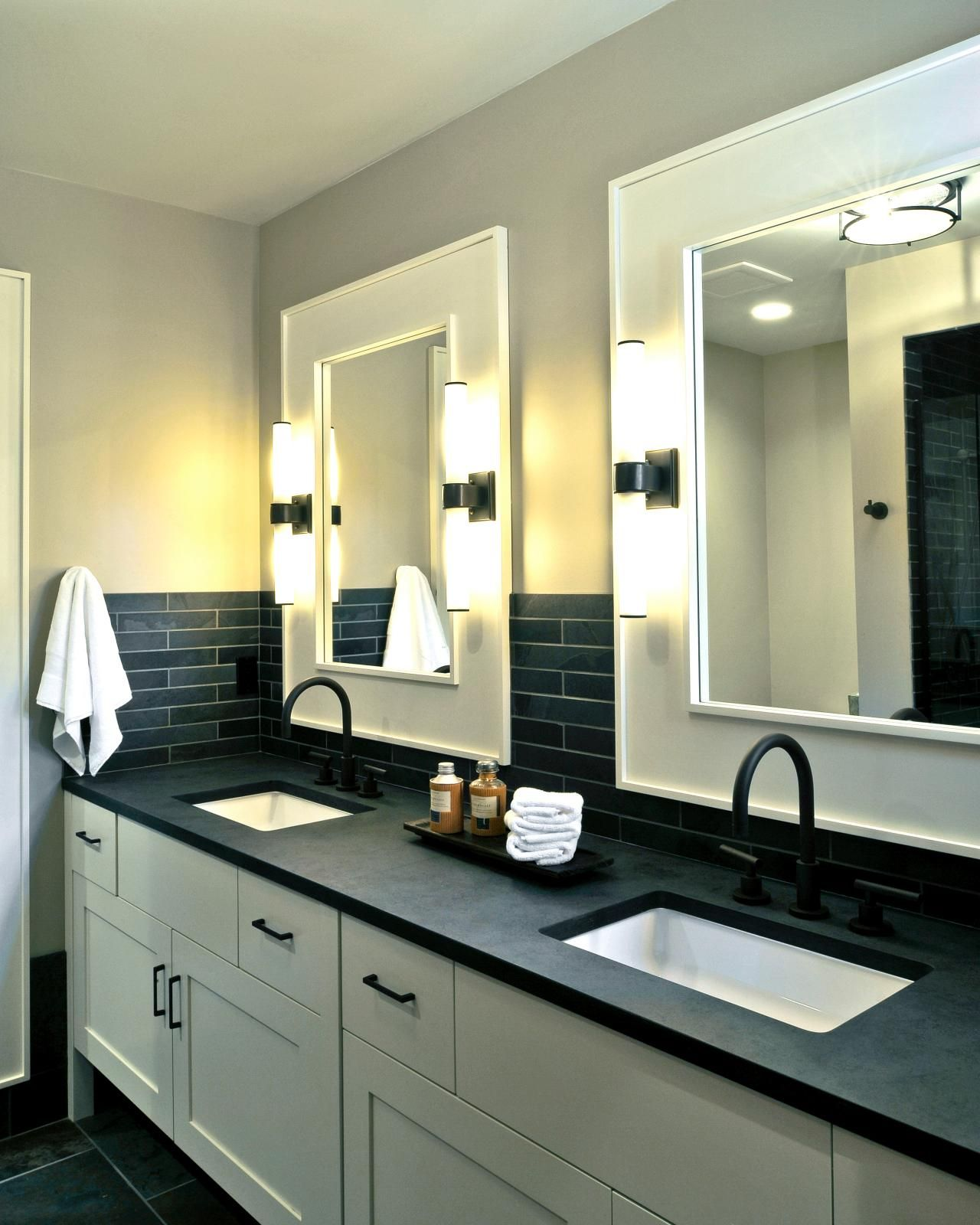 Black and white expertly combine for a compelling, high-contrast look in this contemporary bathroom. Dual sinks and mirrors provide plenty of space for two.