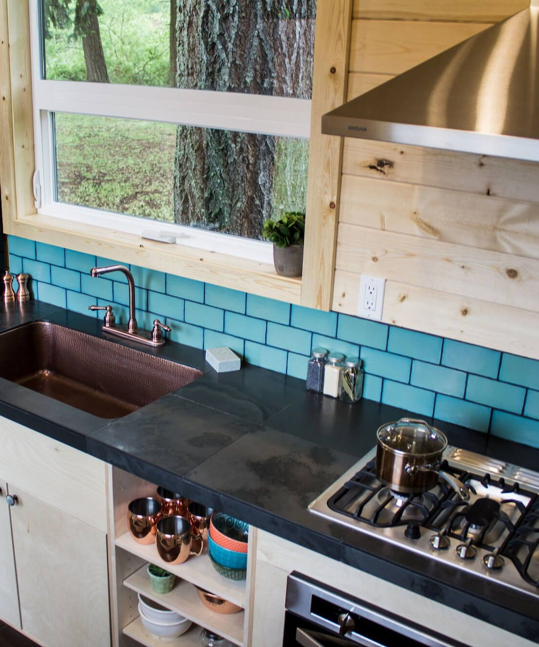 Apothecary by Tiny Heirloom | Black counters, Vent hood and Blue tiles