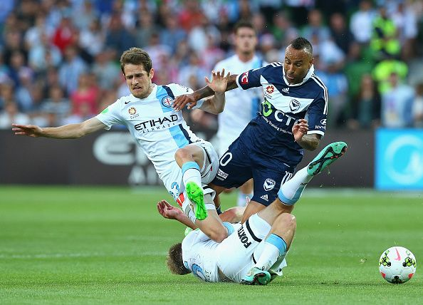 MELBOURNE, AUSTRALIA - DECEMBER 20: Archie Thompson of the Victory is tackled by Mate Dugandzic and Jacob Melling of City during the round 12 A-League match between Melbourne City FC and Melbourne Victory at AAMI Park on December 20, 2014 in Melbourne, Australia. (Photo by Quinn Rooney/Getty Images)