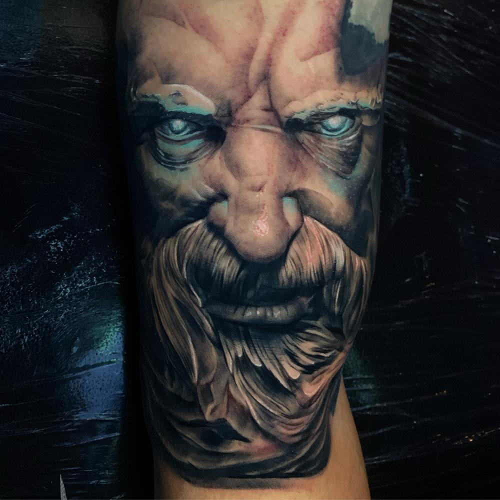 Color-infused black and grey tattoo of a face. Done by award-winning artist Paul Aramayo. #portraittattoo #blackandgreytattoo #realismtattoo #blackandgreyrealism #colorinfusedblackandgrey