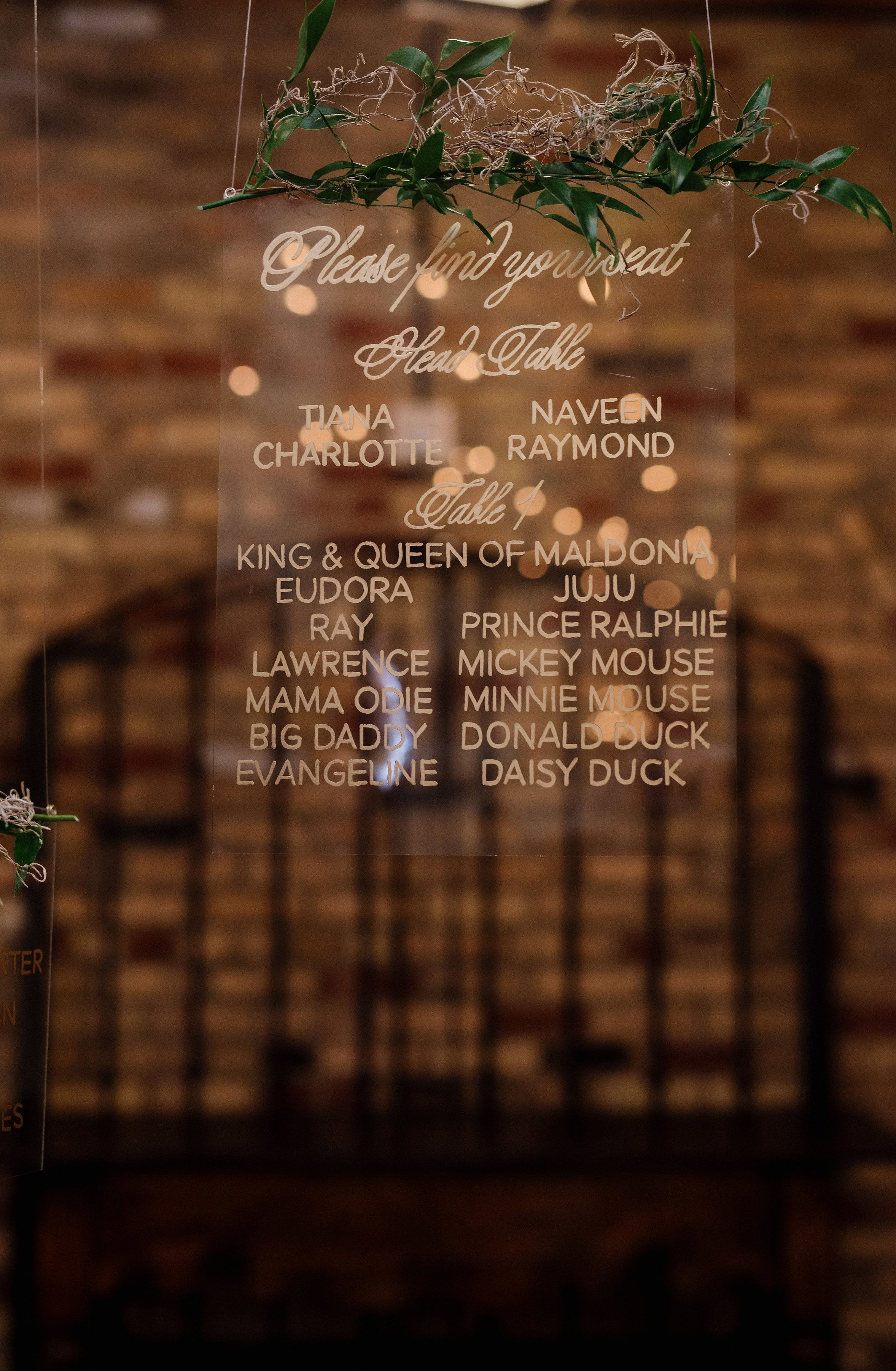 Dreamy hanging acrylic seating chart with lush greenery and gold calligraphy and hand lettering The
