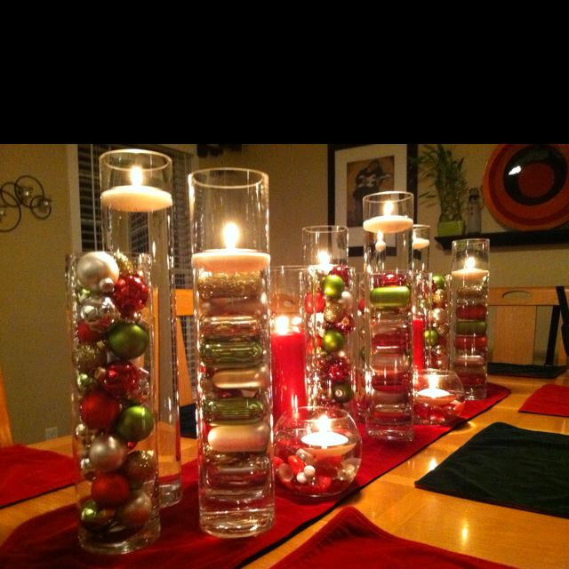 A number of cylinder vases filed with bulbs or water and for Christmas centerpieces for dining room table