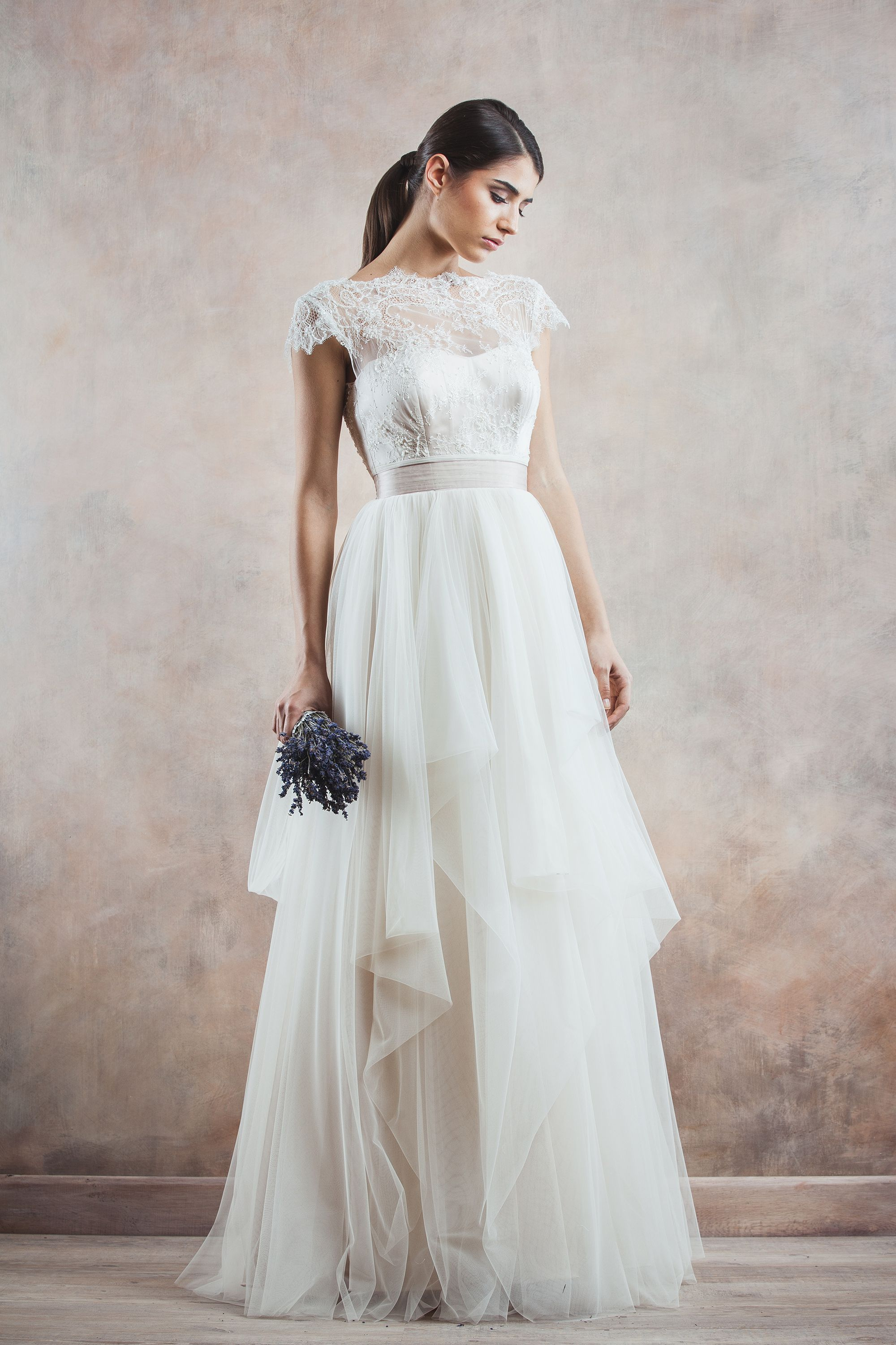 With a figure well-defined by a lavender cordon which delicately passes from the elaborate tulle skirts to the fine, precious lace corset, the Timeea wedding gown is both charming and mysterious at the same time.