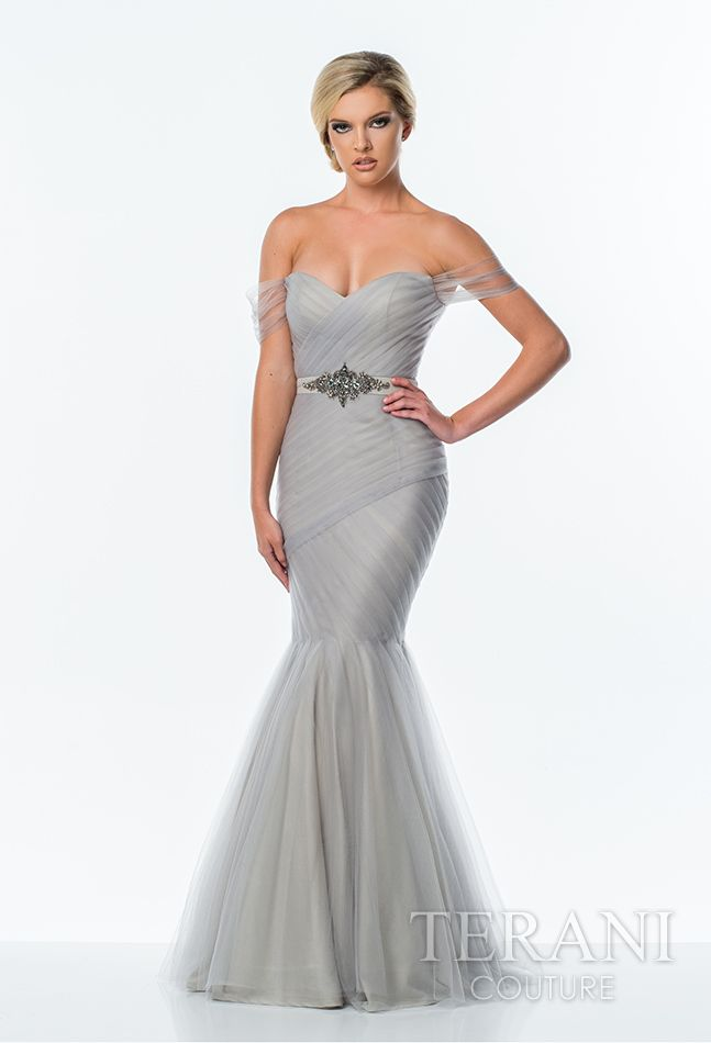 Soft tulle off the shoulder trumpet gown featuring a drop waist bodice with pleated mesh-wrap detail, crystal embellished waistline and flared mesh skirt.