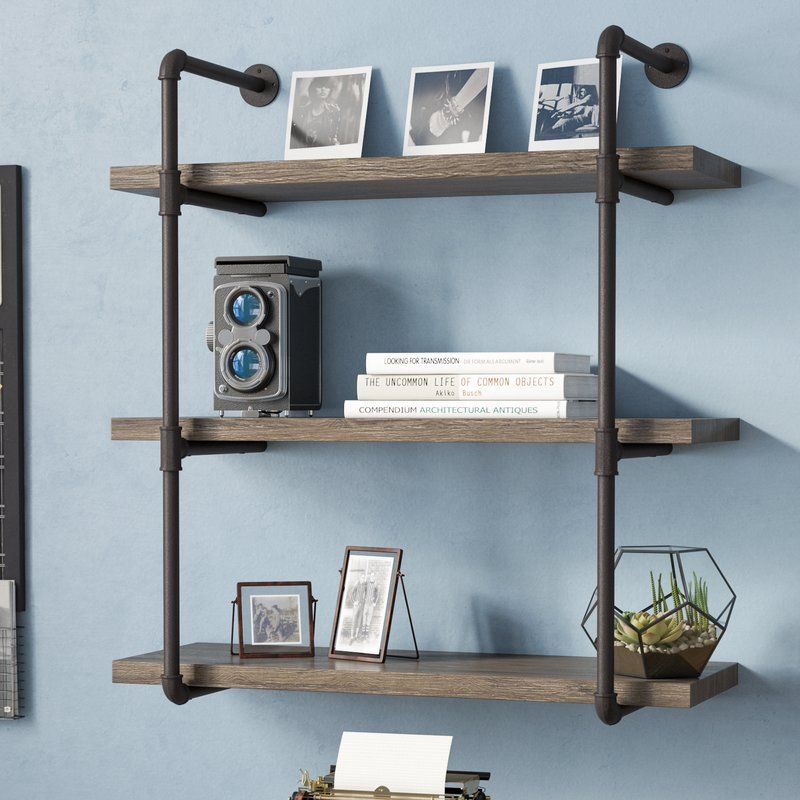Kennard 3 Tier Industrial Pipe Wall Shelf is part of Industrial Living Room Storage - The perfect pick for industrialinspired aesthetics, this floating bookcase features a pipestyle frame awash in a brown finish  Its three tiers of storage space are complete with manufactured wood shelves with am antiqued design for a little rustic appeal in your abode  Display your book collection, photos, plants, your favorite accent pieces, and more! Measures 35'' H x 31 5'' W x 12 5'' D and includes wall mounting hardware for installing flush against the wall