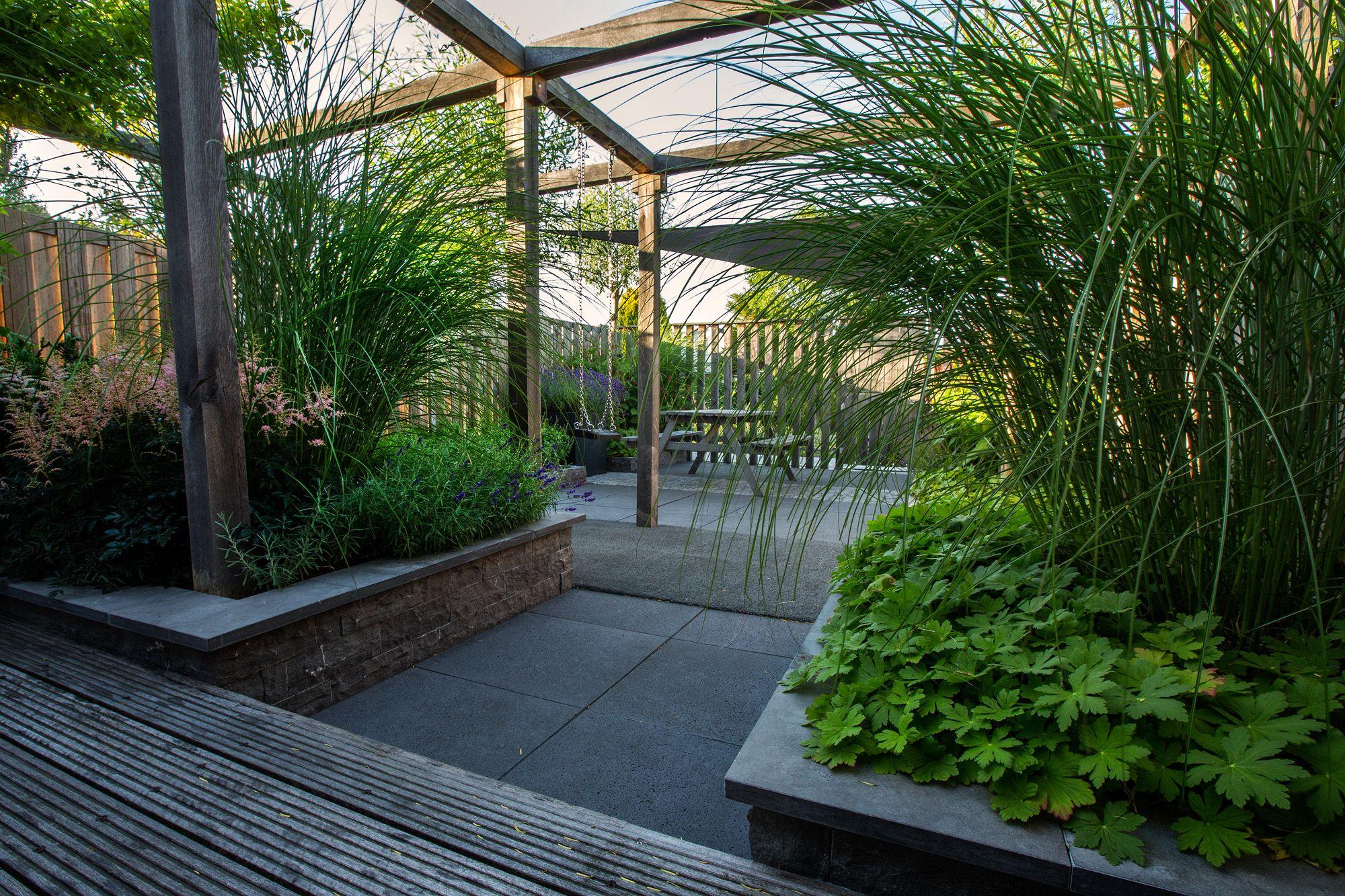 De pergola in deze moderne tuin is mooi en ook nog functioneel