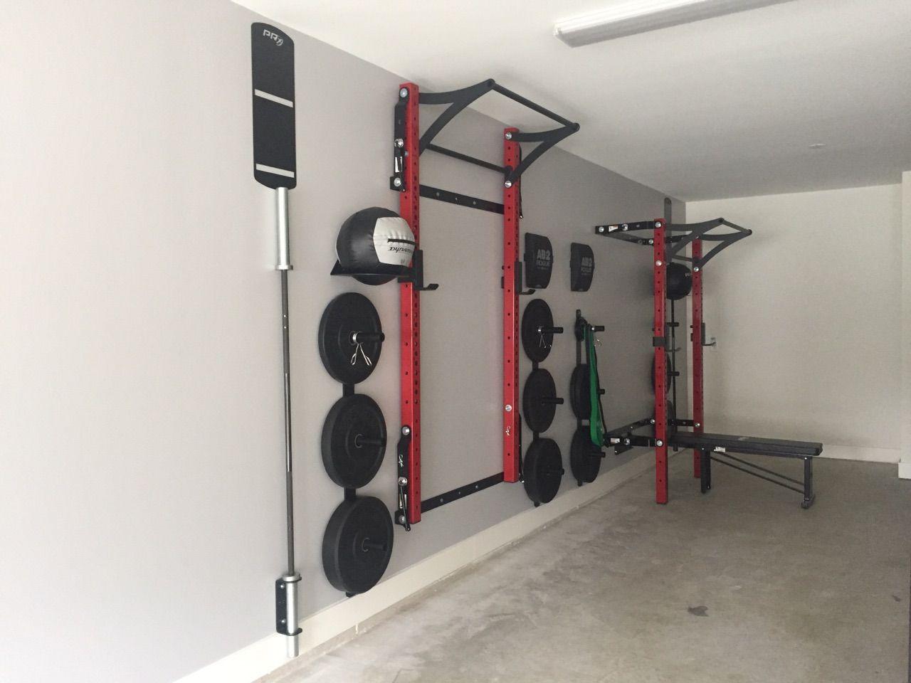 His hers space saving squat racks garage gym in