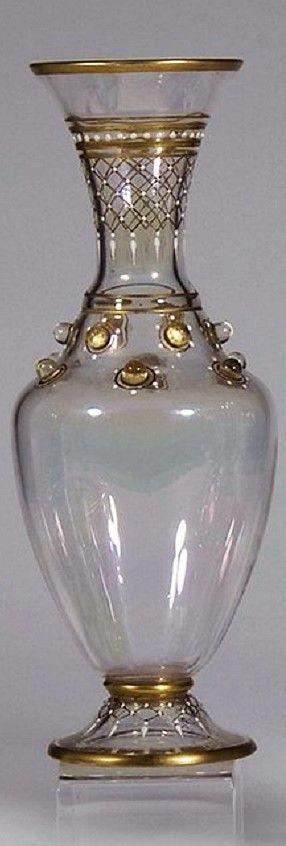 J. & L. Lobmeyr, Wien, um 1880. Farbloses, lüstriertes Glas. Balusterförmiger Korpus mit applizierten Nuppen am Halsansatz. Auf dem Fuß und dem Röhrenhals in Poliergold und weißem Opakemail netzartig dekoriert. Geweitete Mündung. Eine Vase unter dem Boden mit dem Lobmeyr-Signet bezeichnet (Goldmalerei). Eine Vase am Stand min. best. H. 19,5 cm #bodenvasedekorieren