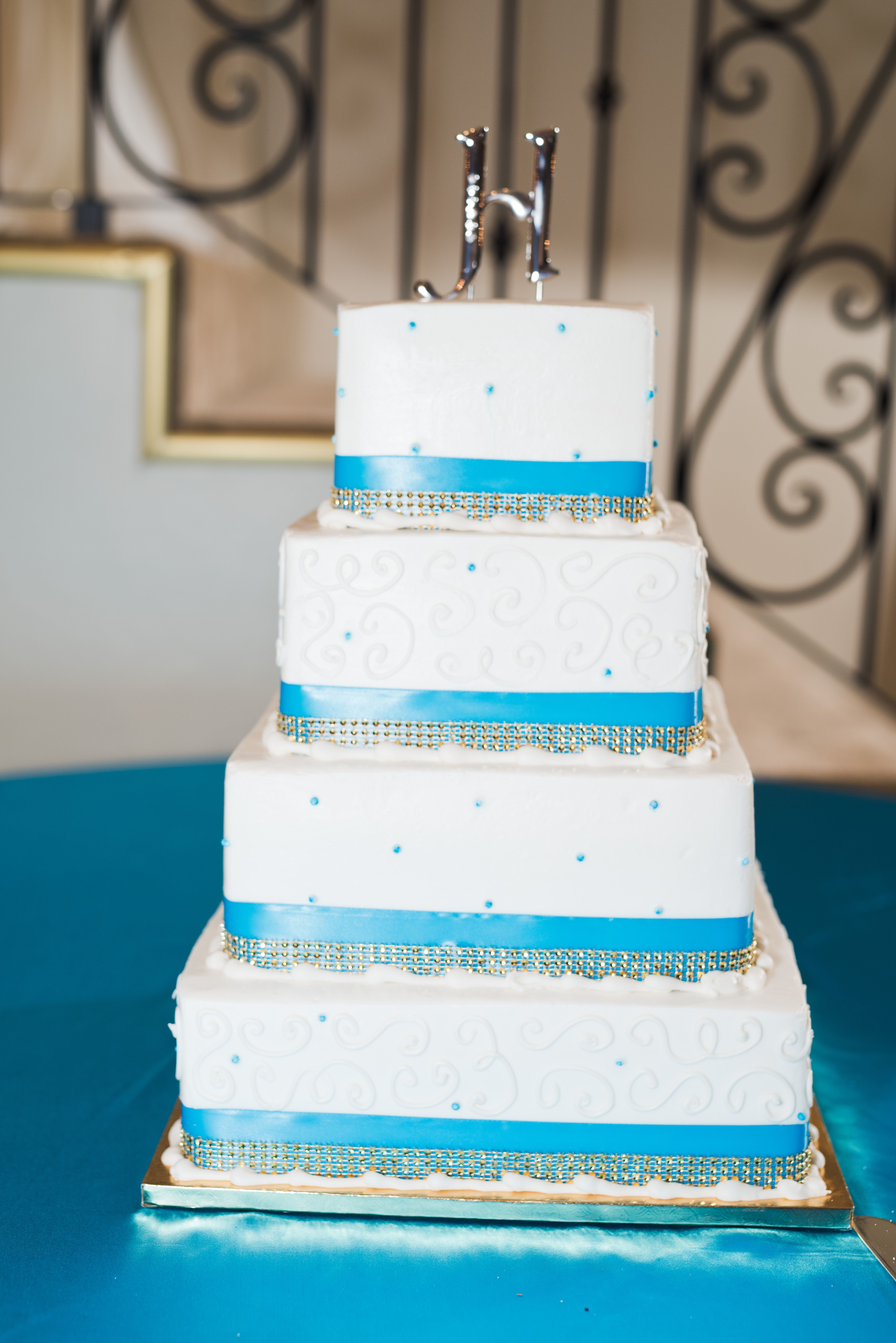 White, four tier cake with diamond and blue trim on each layer ...