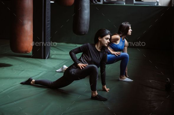 Two beautiful young girls doing fitness in a gym. Stretching the muscles of the back and legs by sim...