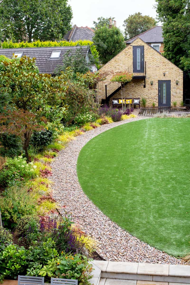 Back garden design featuring oval-shaped lawn, pebble path ...