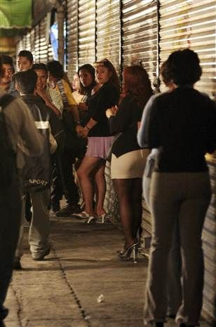 Prostitutes wait for clients at a street in the Merced