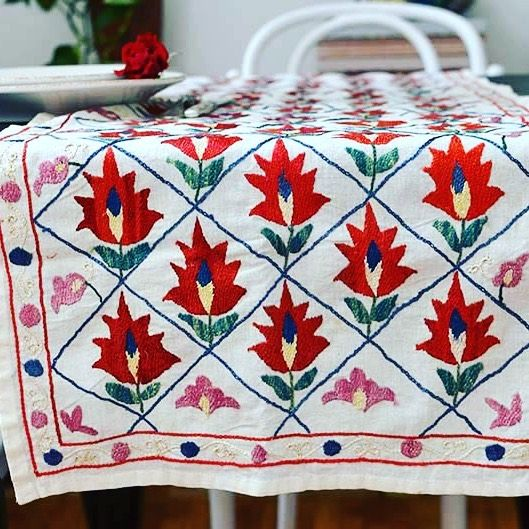 Red and white floral suzani used as a festive tablerunner