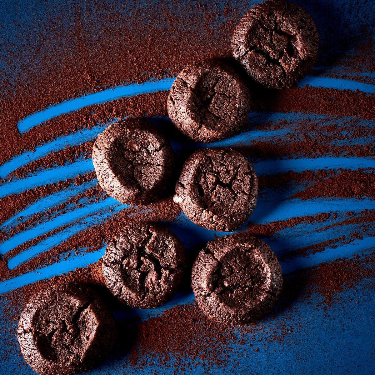 Hacher finement le chocolat, tamiser farine et cacao. Mélanger le beurre mou, le sucre, la cassonade, la fleur de sel, la vanille, incorporer la poudre farine-cacao, le chocolat, malaxer rapidement du bout des doigts jusqu'à l'obtention d'une pâte sablée. La diviser en trois, former des boudins de 4 cm de diamètre et 40 cm de long, les enrouler dans du film transparent et laisser 2 heures au réfrigérateur. Préchauffer le four à 170 °C. Retirer le film des boudins et détailler la pâte en…