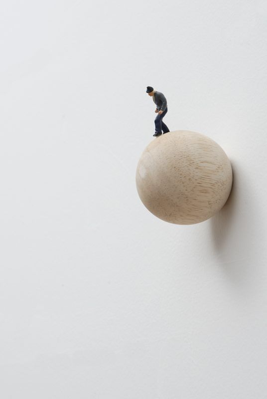 To Jump  (2009), 3 1/2 X 2 1/2 X 2 1/2 in.  , Wooden sphere with figurine (wall installation) // By Liliana Porter