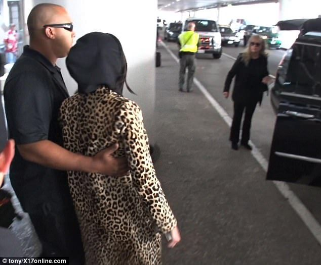 Facing reality: Her jacket pulled up over her hair, Kendall was helped past onlookers by a security guard