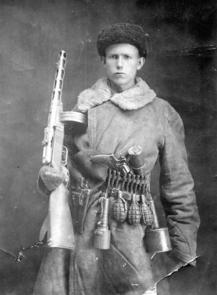 Alexander Ivanov, a regimental intelligence officer, poses for a portrait with his PPsh SBG and a collection of grenades, both anti-personnel and anti-tank. He also carries an ammo belt and two revolvers. No doubt he was well prepared for any eventuality.