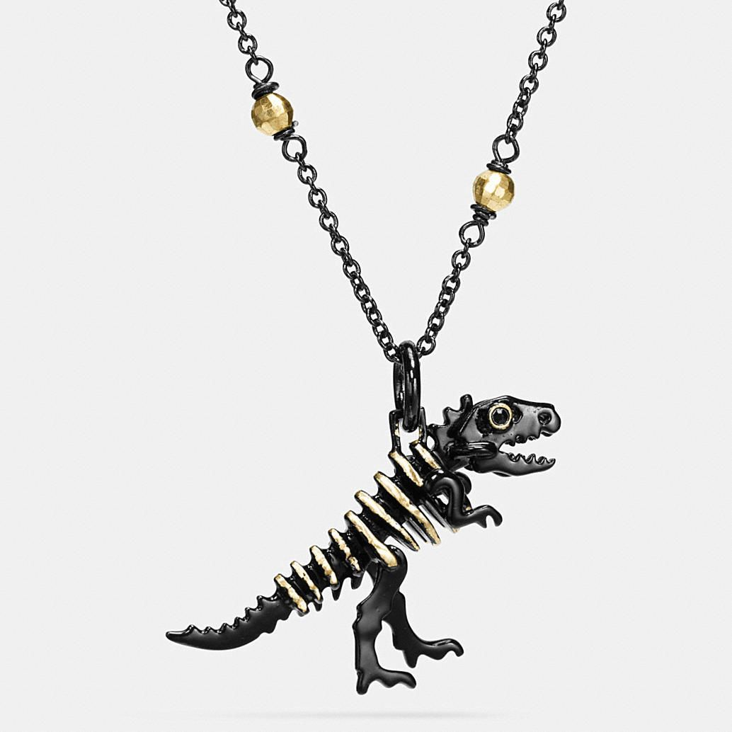 An edgy dinosaur charm with lustrous Swarovski crystal eyes dangles from a slender ionized-plated metal chain on this darling design. Delicately placed gold accents add dimension and contrast.