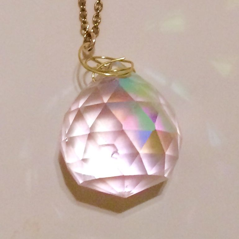 This handmade and self-designed pendant necklace literally shines. The crystal prism looks different in every kind of lighting, and scatters beams of light onto you as you wear it. On a long gold chain, it really makes a statement.   Each order will receive a discount code for next purchase!