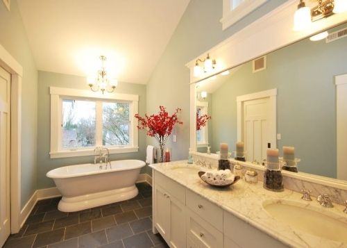 l like the doors, the large trimmed mirror with the sconces installed on it, the window above the mirror, the shape of the cabinets and the vaulted the ceilings.