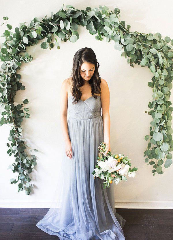 arch made of eucalyptus leaves hung on wall as wedding ceremony backdrop