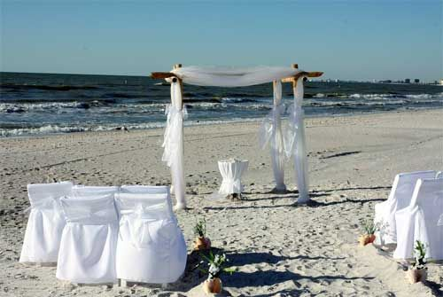 All in white - chairs covers, chair sashes,  arch, unity table and even white flowers as aisle markers