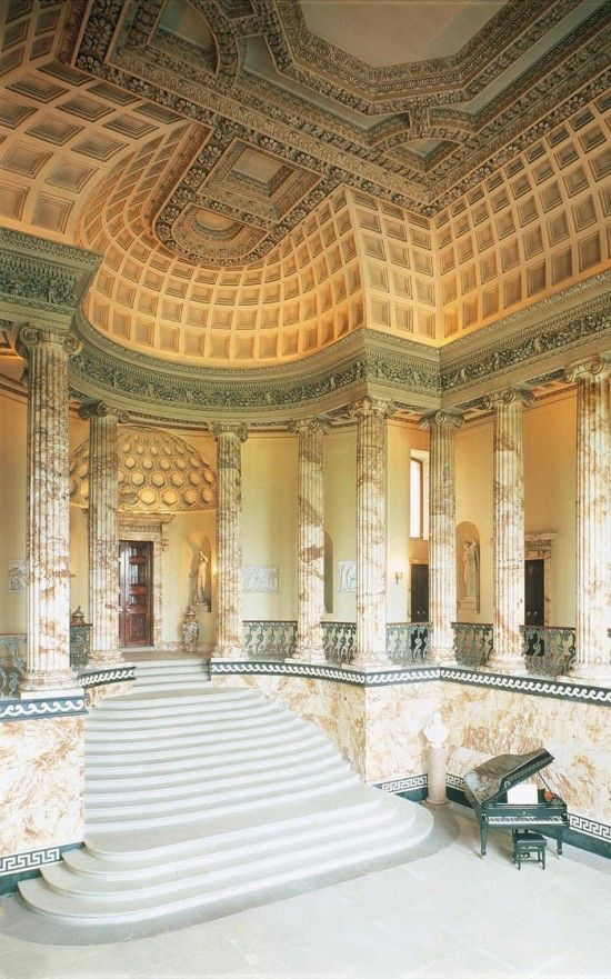 The vertical emphasis and arched ceiling are all Roman. The staircase also looks Roman with its somewhat shallow, white stone steps.