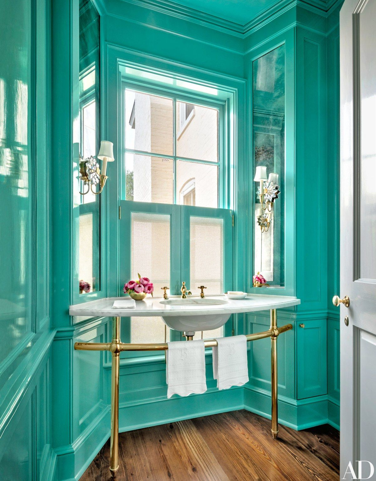 The powder room's sconces are by Chameleon Fine Lighting, and the washstand has brass sink fittings by Waterworks; the walls and ceiling are painted in a high-gloss Sherwin-Williams turquoise.