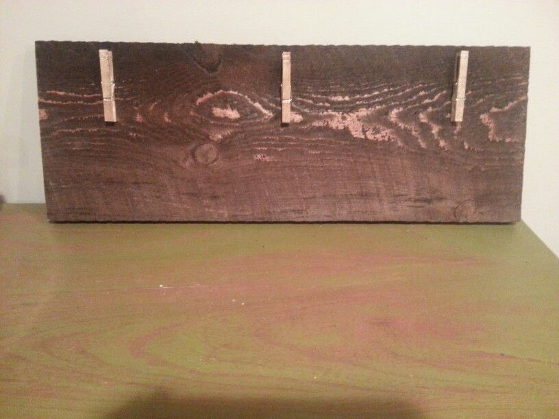Old ruff cut piece of wood turned into picture or note holder using clothes pins