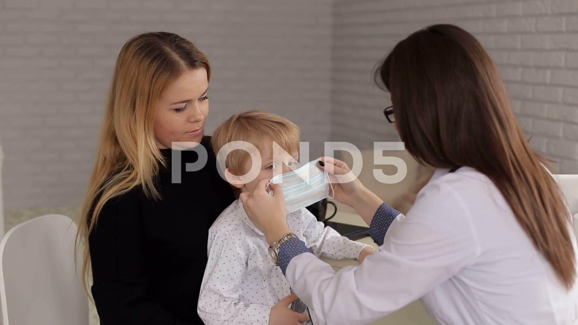 Closeup of a little boy in a medical mask at a reception at the pediatrician Stock Footage medicalmaskCloseboy
