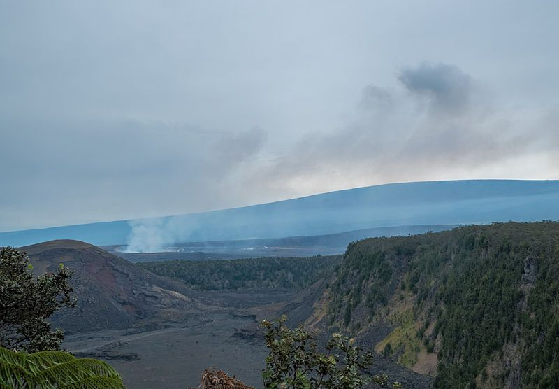 View from the edge of Kilauea Iki: across the caldera Halemaumau Crater lies smoking on the left, and Mauna Loa towers above in the background