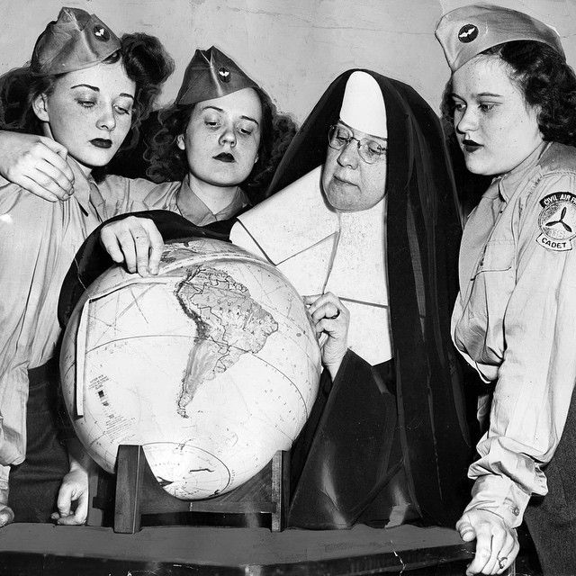 Sister Mary Evarista of Mercy High School with students (from left) Eileen Finnegan, Mary Rita Burke and Hope Worrell in April 1945. The original caption says Sister Mary was teaching an aviation course to the Civil Air Defense cadets, using a tape measure on a globe to determine potential flying routes. #wwII #mercy #aviation #1940s