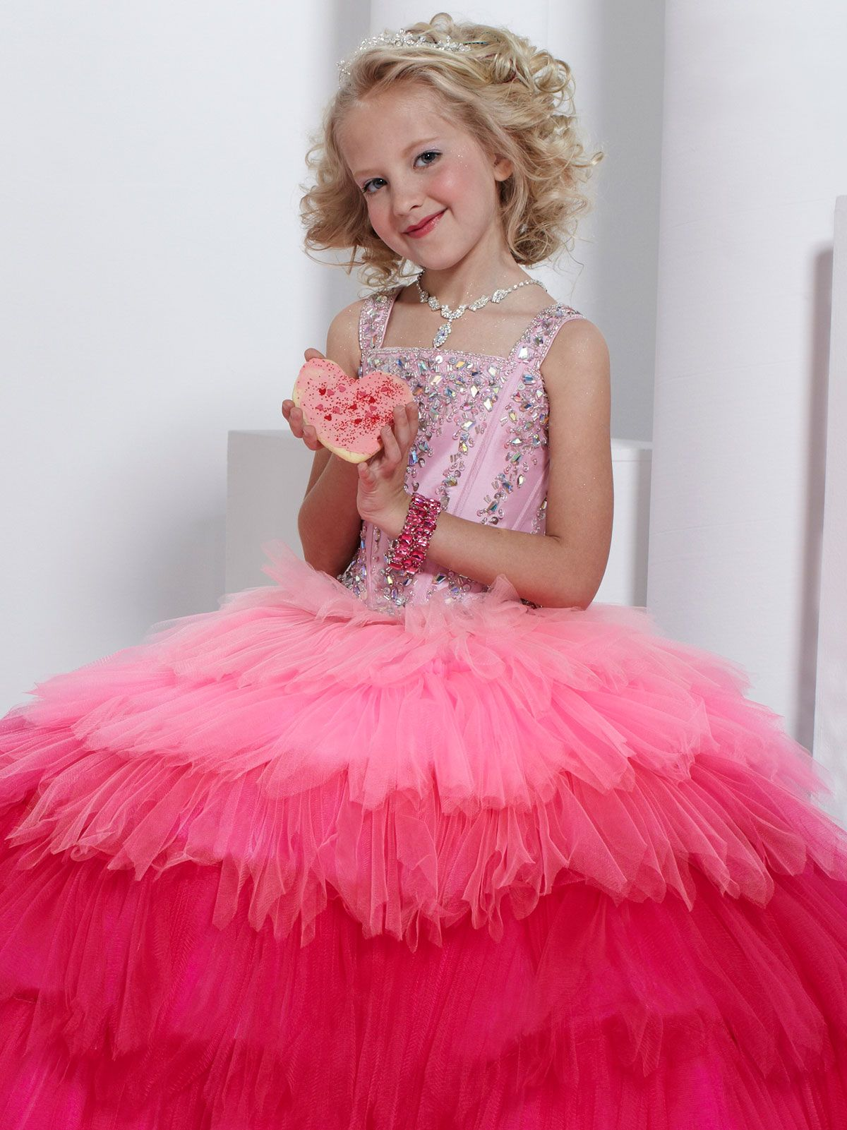 Cute Tiffany Princess Pageant Dress 13317. This taffeta and tulle pageant gown features wide tank straps, square neckline, and beaded and embroidered bodice. Completing the look of this pageant dress is a tiered ball gown skirt. This sweet dress will make your girl feel like a princess. Available in Fuchsia/Pink and Peacock/Sky.
