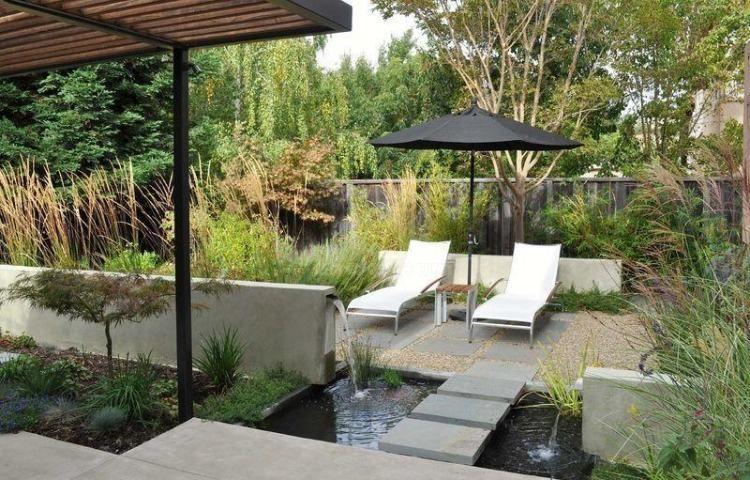 Cascade de jardin moderne près de la terrasse avec parasol et bains de soleil