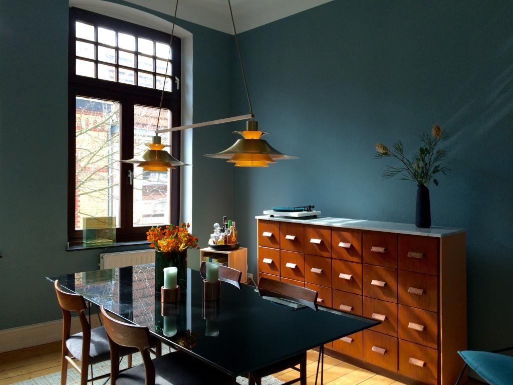 Schönes Esszimmer im Vintage Stil mit warmer Beleuchtung und blau gestrichenen Wänden.  ...