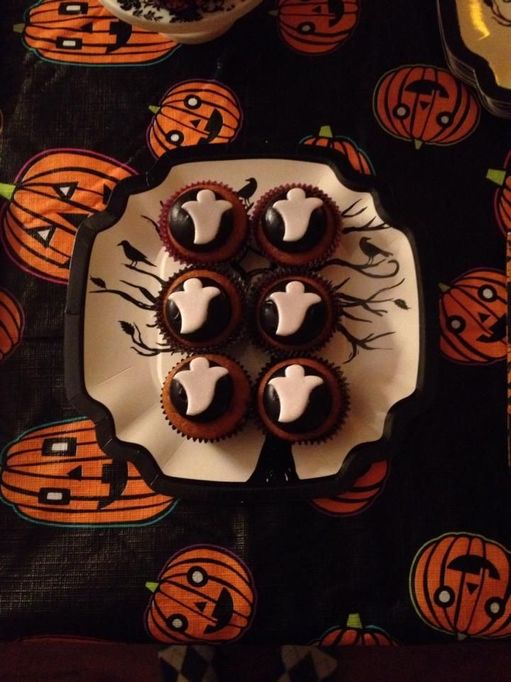 Our Halloween/Housewarming Party: Pumpkin cupcakes with chocolate marshmallow frosting (dyed black) topped with white fondant ghosts. I used the center shapes from my Wilton Halloween Linzer Cutter set, and brushed my ghosts with white pearl dust. Loved how these ghosts turned out!