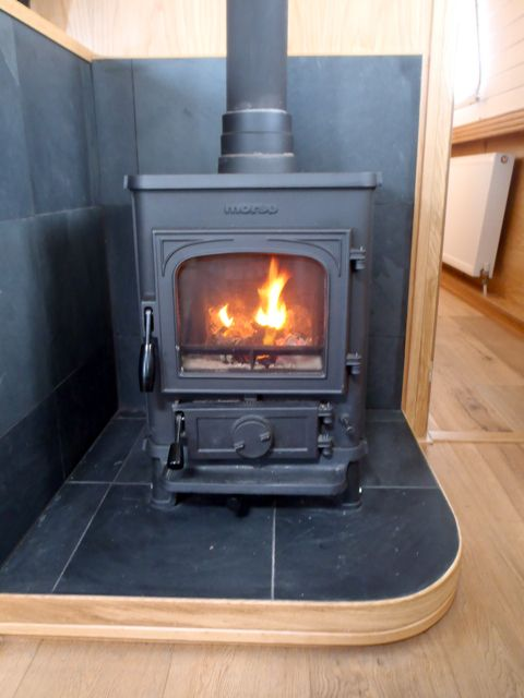 This solid fuel stove is set on a fireplace made of slate tiles