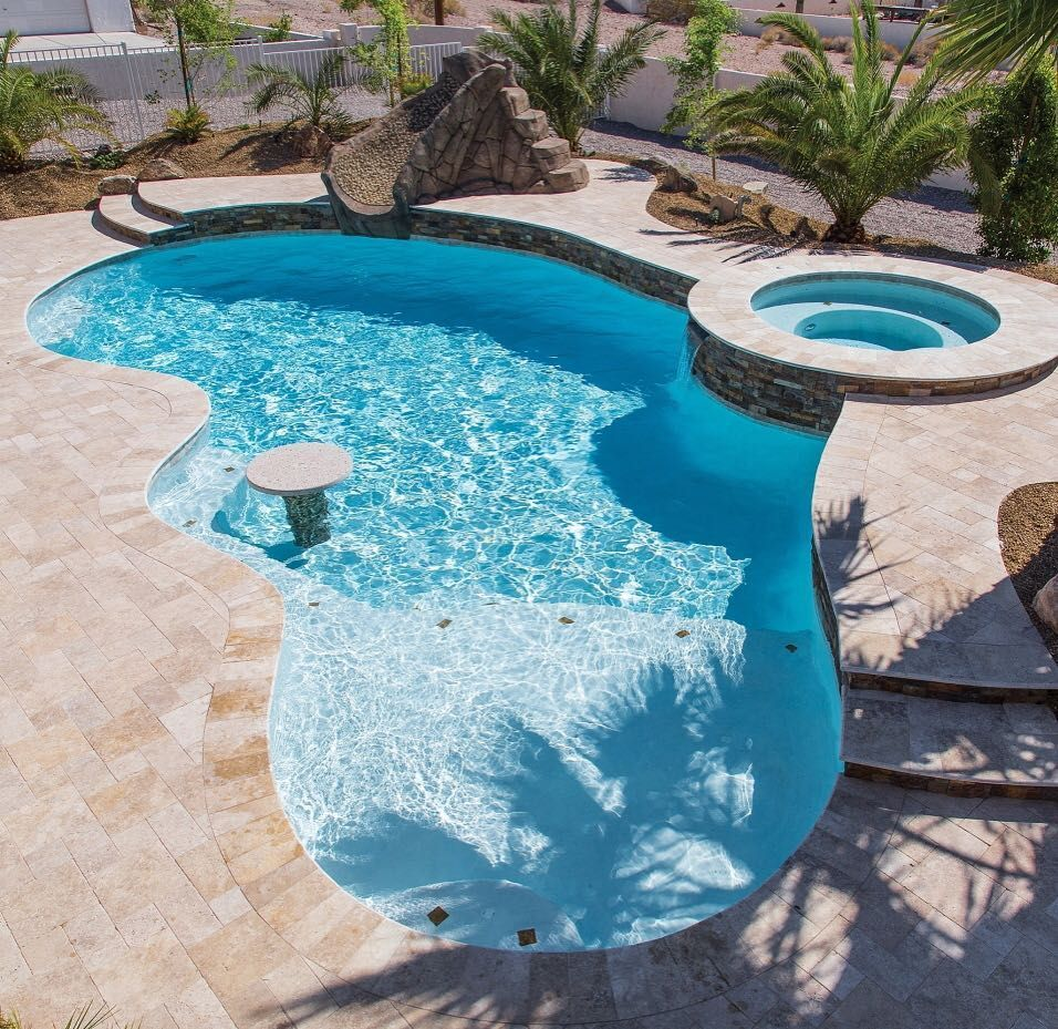 Here is a lovely free form pool with a round table in the pool, a ...
