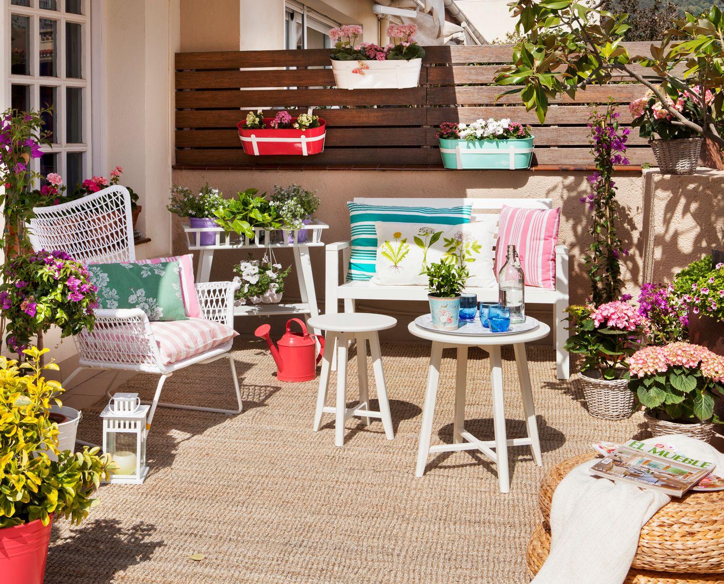 Terraza con alfombra de sisal macetas flores y cojines - Cojines para terraza ...
