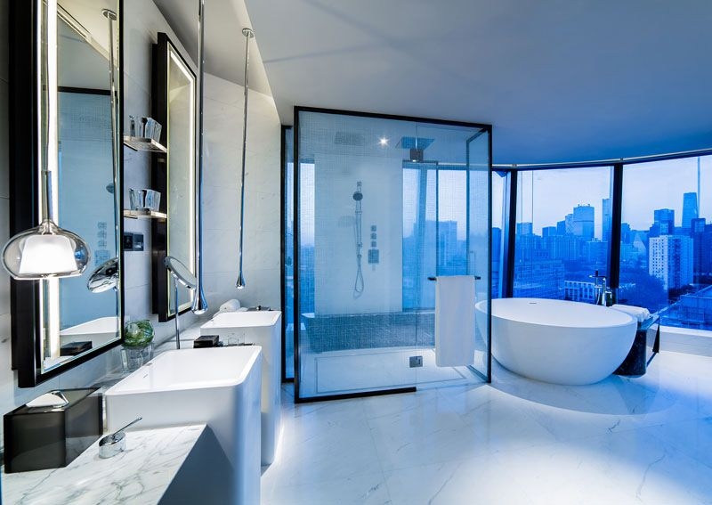 in this modern hotel bathroom a white standalone tub sits in front of the glass enclosed large shower and faces the city of beijing the bathroom decor is