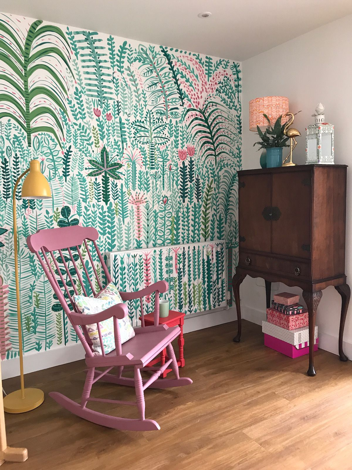 Wall mural with a tropical jungle print painted by designer Lucy Tiffney. part of an interior design by Sophie Robinson for DIY SOS