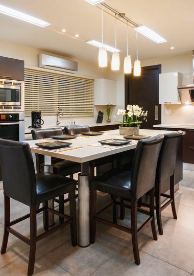 Una cocina llena de iluminación y un desayunador con muebles ...